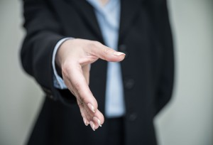 Woman in business suit holding out her hand to shake